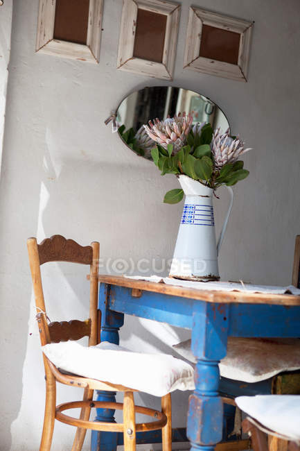 Vase with flowers on table, mirror on wall in room — Stock Photo