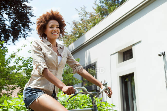 Woman riding bicycle outdoors — Stock Photo