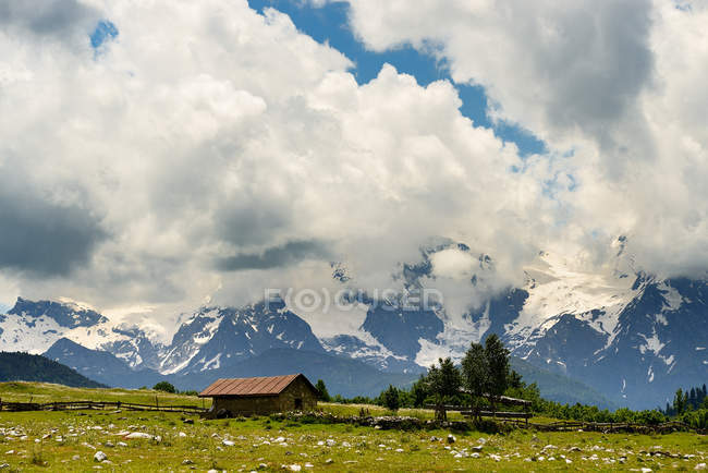 Barn and distant mountains under blue cloudy sky — Stock Photo