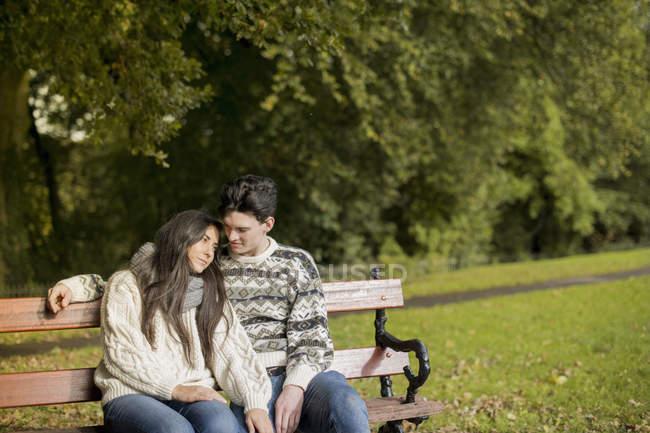 Pareja joven sentada en el banco del parque - foto de stock