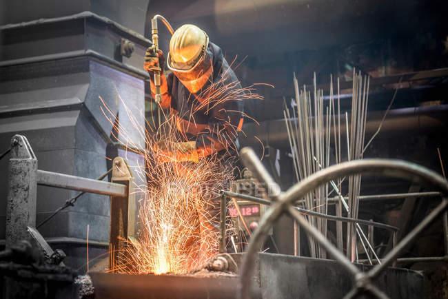 Travailleur de l'acier au milieu des étincelles de l'acier fondu dans la fonderie industrielle — Photo de stock
