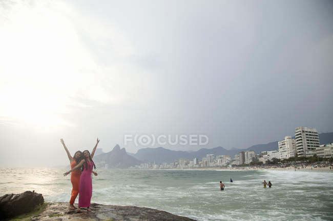Portrait of two young women with arms raised on Ipanema beach, Rio De Janeiro, Brazil — Stock Photo