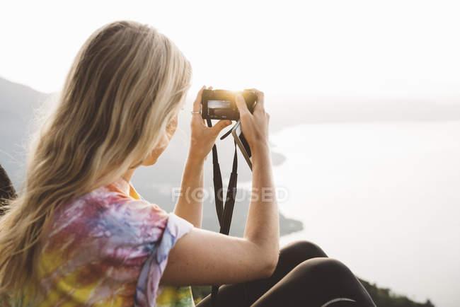 Junge Frau fotografiert am atitlan-see mit digitalkamera, guatemala — Stockfoto