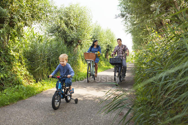 Family cycling down on country lane — Stock Photo