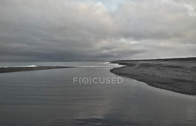 Lake with empty shores and clouds — Stock Photo