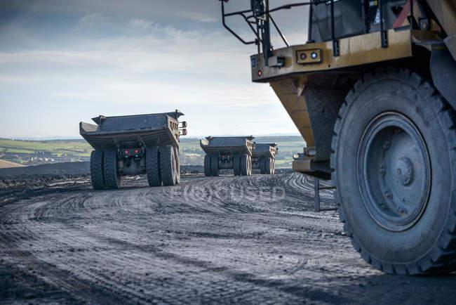 Dumpers conduisant sur la voie à la mine de charbon à ciel ouvert — Photo de stock