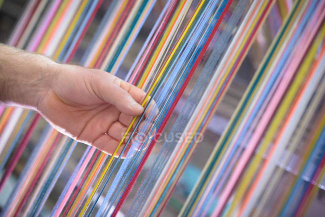 Worker adjusting multicoloured silk yarn on industrial loom in textile mill — Stock Photo