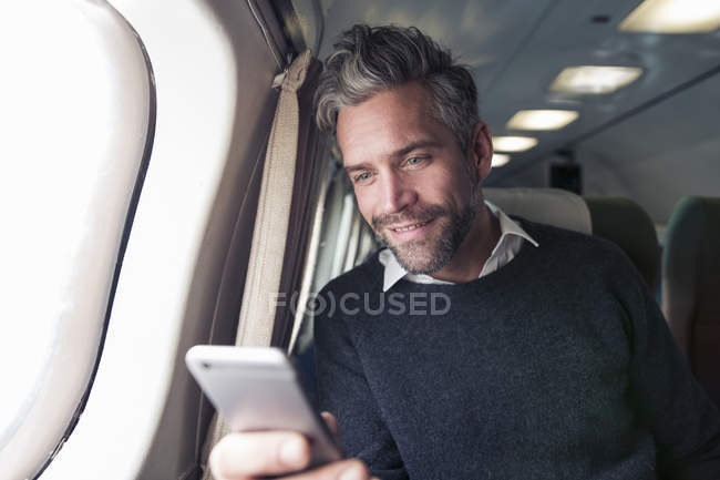 Mid adult man on airplane, using smartphone — Stock Photo