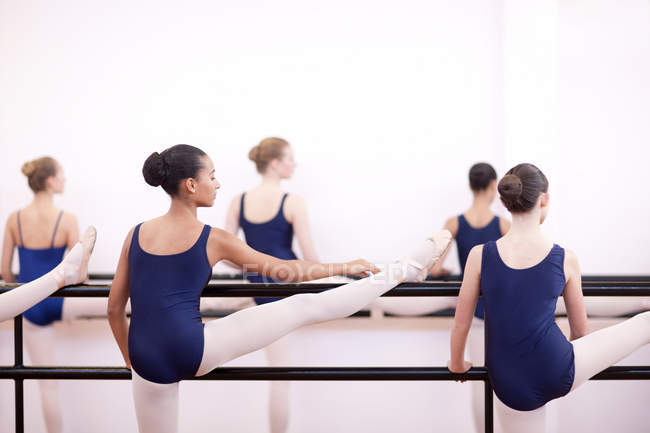 Teenage ballerinas practicing at barre — Stock Photo