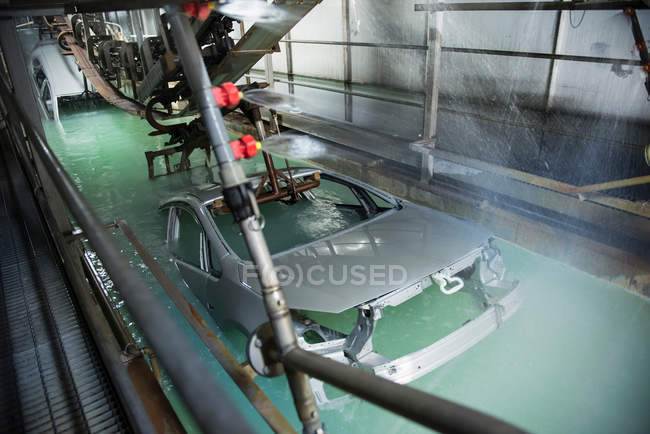 Car bodies being dipped in car factory — Stock Photo