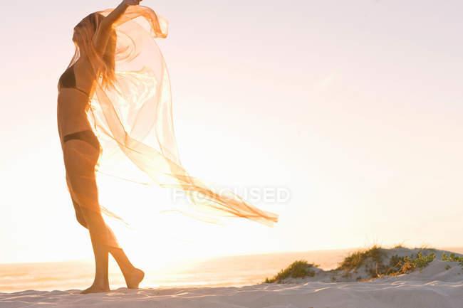 Woman playing with sarong on beach — Stock Photo