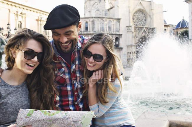 Туристична друзів, дивлячись на карту, Plaza de la Вірхен, Валенсія, Іспанія — стокове фото