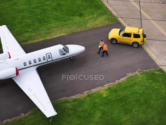 Инженеры с реактивными самолетами на взлетно-посадочной полосе — стоковое фото