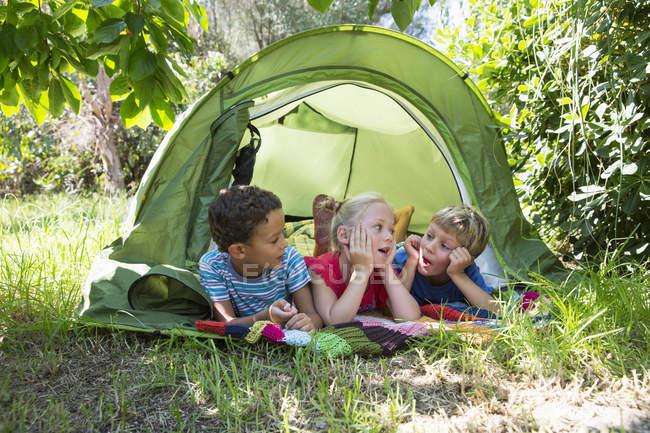 Three children chatting in garden tent — Stock Photo