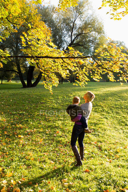 Mother holding son in park — Stock Photo