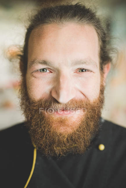 Portrait of bearded mid adult man looking at camera smiling — Stock Photo
