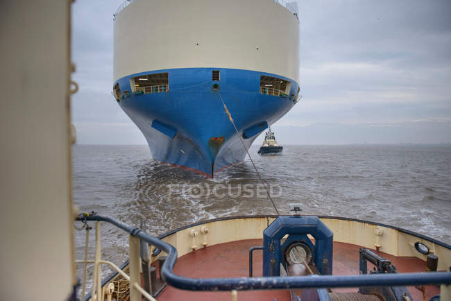 Tug towing car ship with rope out at sea — Stock Photo