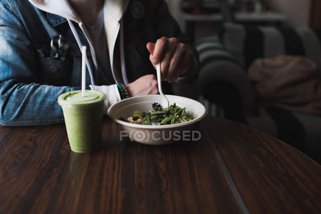 Юнак сидячи за столом, їдять салат, середині розділі — стокове фото