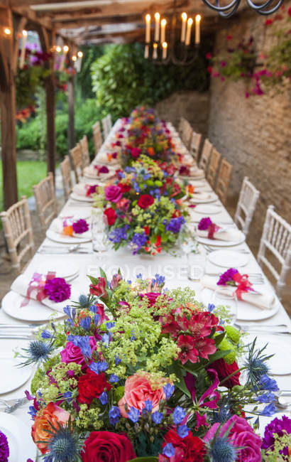 Diminishing perspective view of long table decorated with flowers — Stock Photo