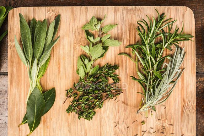 Board with whole leaves herbs — Stock Photo