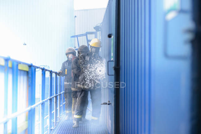 Three firefighters using hose in fire simulation training facility, front view — Stock Photo