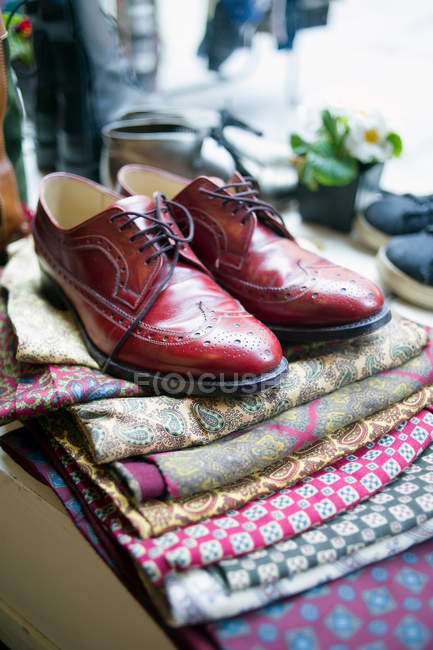 Vintage red brogue shoes on top of fabric pile — Stock Photo