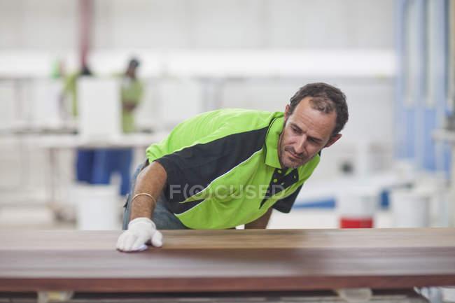 Карпентер, проверка качества древесины в мастерской — стоковое фото
