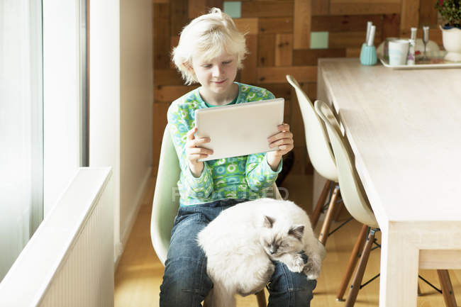 Boy with cat on his lap using digital tablet in kitchen — Stock Photo