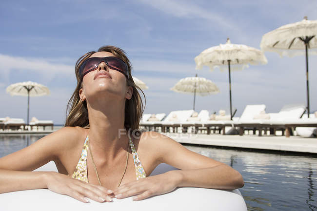 Cool young woman wearing shades leaning against poolside at beach resort, Majorca, Spain — Stock Photo