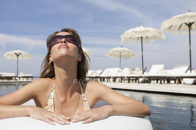 Giovane donna fredda indossa sfumature appoggiato a bordo piscina al beach resort, Maiorca, Spagna — Foto stock