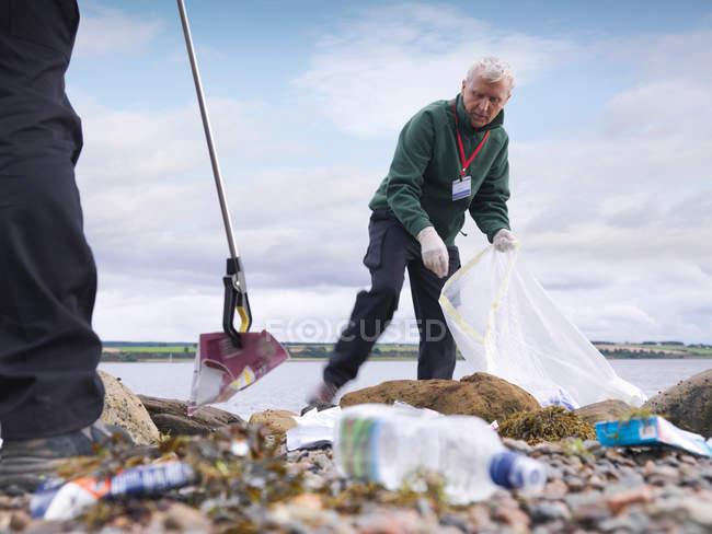 Deux hommes environnementalistes enlevant la litière du bord de la mer — Photo de stock
