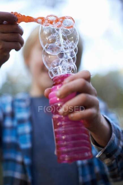 Garoto segurando garrafa de bolhas, close-up — Fotografia de Stock