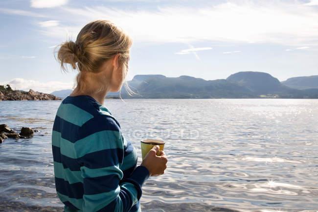 Жінка з кавою на морі й в горах. — стокове фото