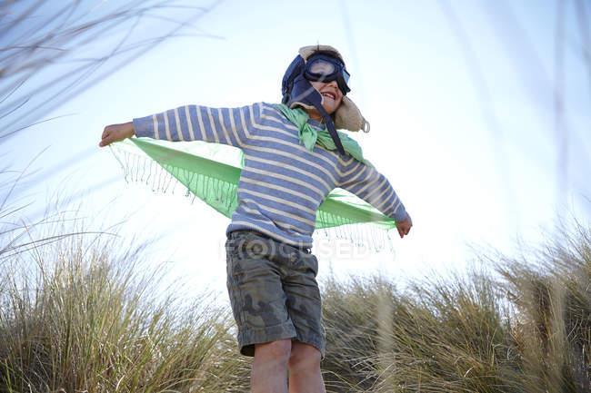 Молодий хлопчик на пляжі, носіння костюмований, роблячи вигляд, що літають — стокове фото