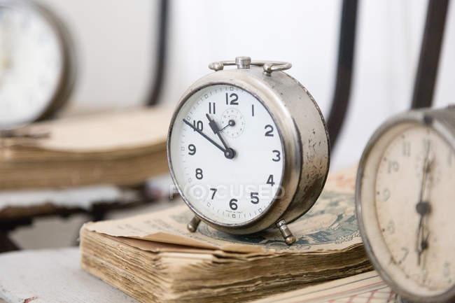 Close up of vintage alarm clocks on weathered books — Stock Photo