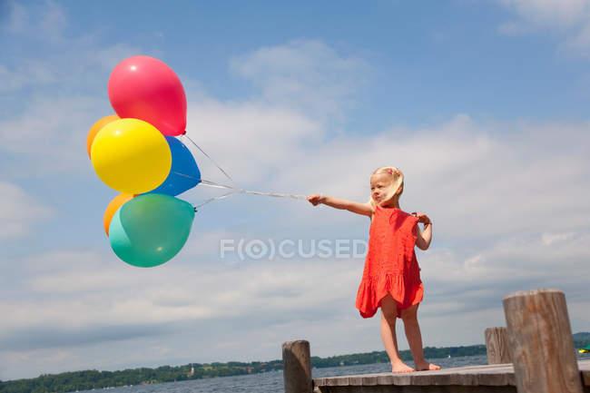 Fille tenant des ballons sur une jetée en bois — Photo de stock