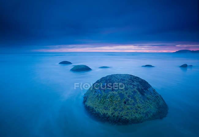 Olas lavándose sobre rocas - foto de stock