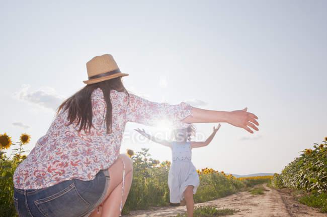 Fille courant à travers le champ à la mère à bras ouverts — Photo de stock