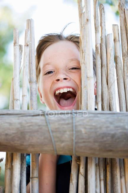 Menino sorrindo atrás da cerca, foco em primeiro plano — Fotografia de Stock