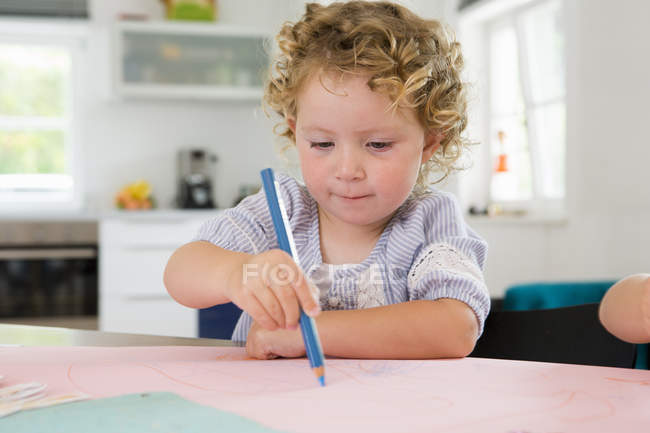 Girl drawing with pencil by table — Stock Photo