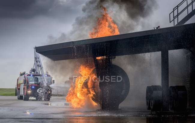 Fire engine spraying water on simulated fire at airport training facility — Stock Photo