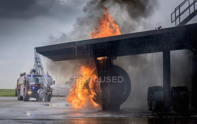 Bomberos rociando agua sobre fuego simulado en instalaciones de entrenamiento del aeropuerto - foto de stock
