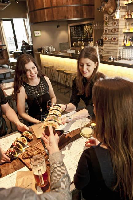 Офіціантка виступає тако на бітстер бар друзям — стокове фото