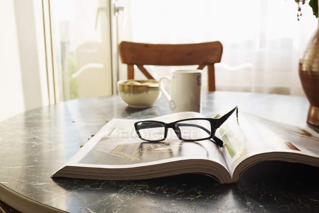 Открытая книга на столе с очками — стоковое фото