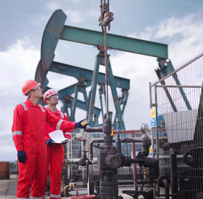 Deux travailleurs prennent une lecture et regardent vers le haut, à côté des pompes à huile au-dessus des puits de pétrole terrestres (hochant la tête aux ânes / pompiers ) — Photo de stock