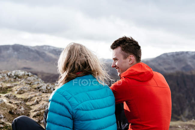 Young couple sitting on hilltop, rear view, Keswick, Lake District, Cumbria, United Kingdom — Stock Photo