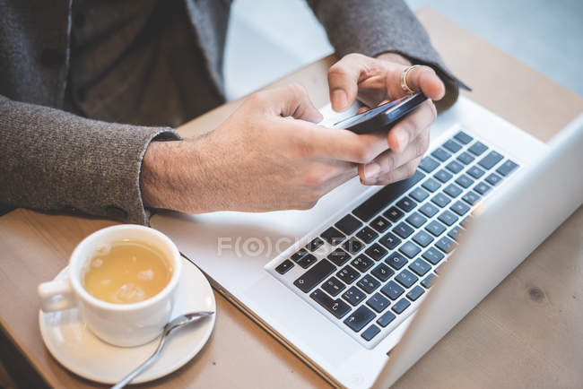Cropped shot of businessman sitting in cafe texting on smartphone — Stock Photo