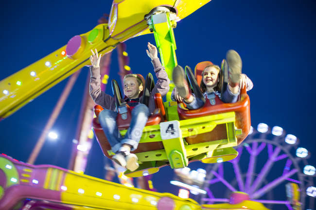 Sister and brother mid air on fairground ride at night — Stock Photo