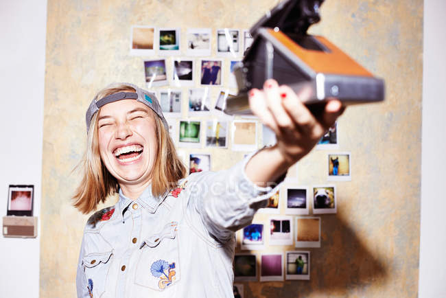 Young woman in front of photo wall taking instant selfie on retro camera — Stock Photo