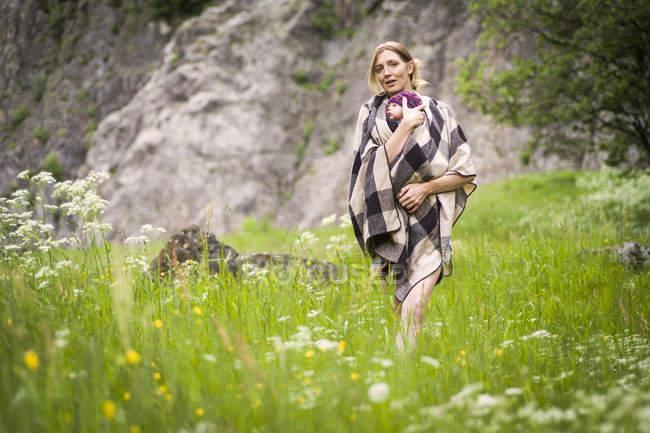Mère portant la chéri par le pré — Photo de stock
